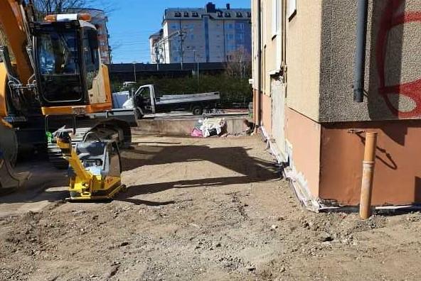Grävmaskin utför schaktarbete för innegårdsrenovering i Stockholm