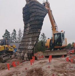 Grävmaskin täcker berg med stockmattor inför sprängning