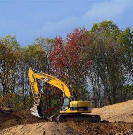 Bandburen grävmaskin justerar slänter på ett byggprojekt