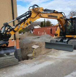 Grävmaskin utför dräneringsarbete i Sollentuna