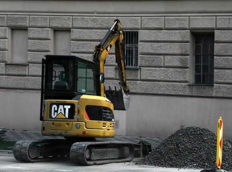 Grävmaskin utför dräneringsarbete för husgrund